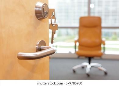 Vacancy job. Half opened door to an office.Door handle, door lock, armchair on wheels inside - out of focus