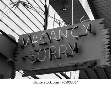 A vacancy sign lit up with sorry beneath.