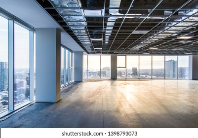 Vacant office space offering views of the city. Open ceiling showing ventilation system. Shot just after construction was completed on a late winter afternoon in downtown Montreal, Quebec, Canada.