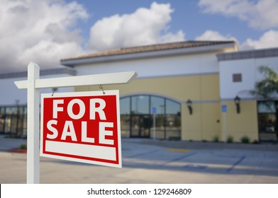 Vacant Retail Building with For Sale Real Estate Sign in Front.