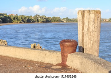 Vacant rusty metal mooring bollard at the pier with ocean background.