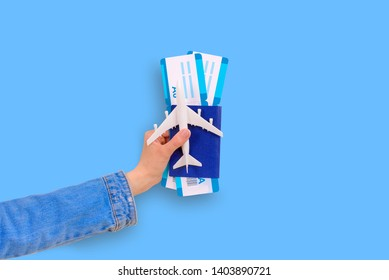 Vacation, air travel. Girl left hand holds passport with boarding pass and plastic plane on blue background. Empty space for design, space for text, flat layer.