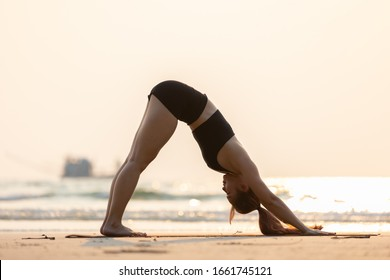 Vacation of Attractive Asian woman relaxing in yoga Downward Facing dog or Adho Mukha Svanasana pose on sand and beach with sunset sea in Thailand Tropical island,Feel comfortable and relax in holiday
