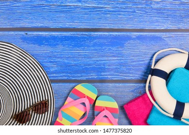 Vacation background with sun hat flip flops and blue wood