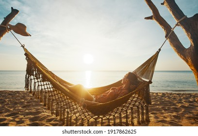 Vacation Beach Summer Holiday Concept. Young woman relaxing in the hammock at sunset, island Phu Quoc, Vietnam.