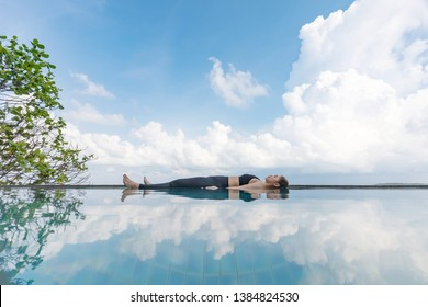 Vacation of Beautiful Attractive Asian woman relaxing in yoga Savasana pose on the pool above the beach with beautiful sea in Tropical island,Feeling comfortable and relax in holiday,Vacations Concept