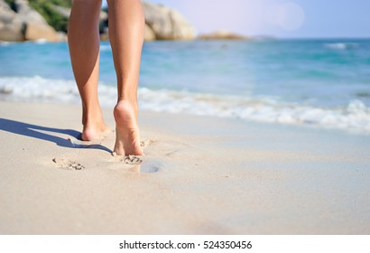 Vacation concept. Close up of female legs walking by the beach.