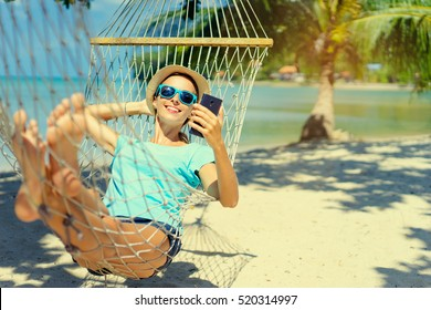 Vacation concept. Enjoying the summer. Young pretty woman in hat and sunglasses using smartphone laying in hammock on the beach.