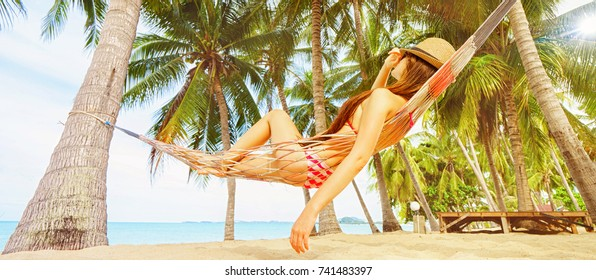 Vacation concept. Enjoying the summer. Young pretty woman in hat and sunglasses laying in hammock on the beach. Banner edition.
