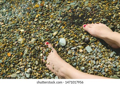 vacation concept of feet on a pebble