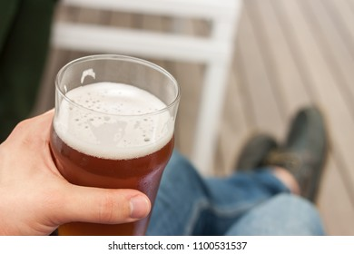 vacation concept hand with glass of beer