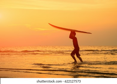 Vacation Concept ; Happy surfer standing with surfboards on the beach, at sunset,Phuket,Thailand