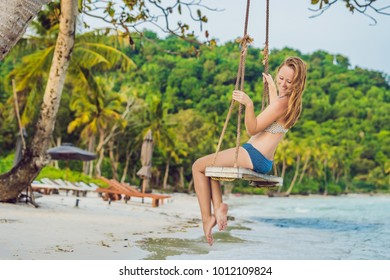 Vacation concept. Happy young woman sitting on swing enjoying sea view.