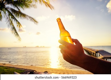 Vacation concept. Male hand holding bottle of beer on the sea beach.