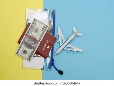 vacation concept. on a yellow-blue background model airplane passport voucher in a plastic transparent bag and dallars. top view