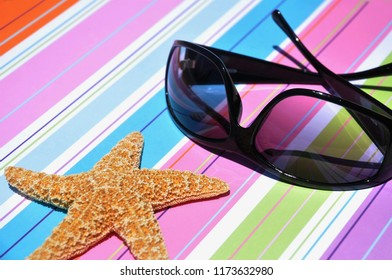 Vacation concept. Sunglasses and starfish on a pretty colorful background.