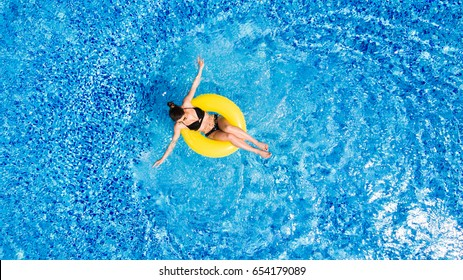 Vacation concept. Top view of slim young woman in bikini on the yellow air inflatable ring in the big swimming pool.