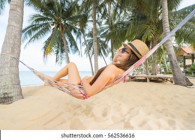 Vacation concept. Young happy woman in hat and sunglasses laying in hammock on the tropical beach.