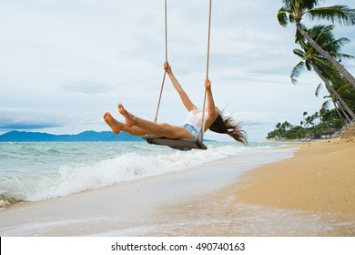Vacation concept. Young woman  swing on a beach swing. Selective focus. Hairs in motion blur.