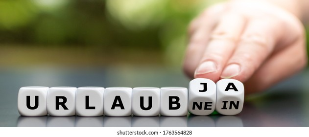 "Vacation despite the Corona virus? Hand turns dice and changes the German expression ""Urlaub nein"" (vacation no) to ""Urlaub ja "" (vacation yes). - Shutterstock ID 1763564828"