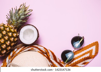 Vacation female stuff, summer flat lay: straw hat, sun glasses, sunscreen cream, tropical fruits on pink background. Copyspace for text. top view, flat lay