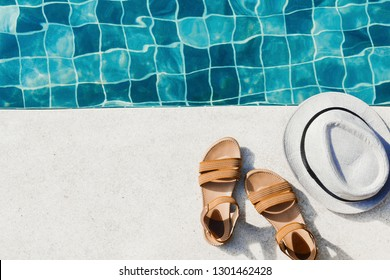Vacation flat lay with woman's sandals and hat front of the pool