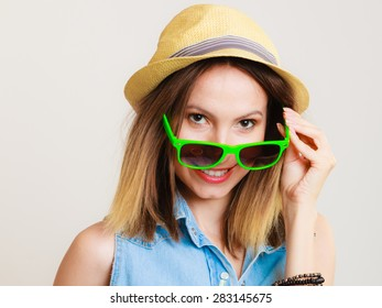 Vacation. Happy girl in summer clothes sunglasses and straw hat. Portrait of smiling woman tourist on gray.