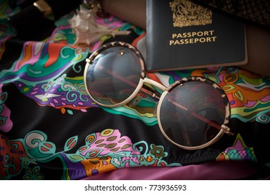 Vacation or holiday objects including passport, sunglasses and paisley swimsuit. Stylish women's items ready to go for vacation. Warm weather travel, tropical trip to paradise. Lay flat accessories.