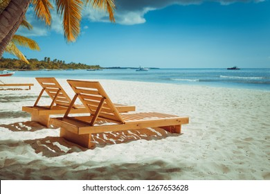 Vacation holidays background wallpaper - beach loungers without people in sunny tropical caribbean beach with white sand in dominican republic at island saona in retro style