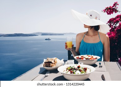 Vacation. Holidays. Eating. Young woman in dress and hat is enjoying the sun, sea view and tasty food