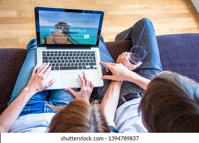 Vacation holidays planning with couple searching hotel resorts online on website for getaway destination, two people sitting on couch choosing best travel deals
