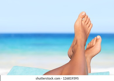 Vacation holidays. Woman feet closeup of girl relaxing on beach on sunbed enjoying sun on sunny summer day.