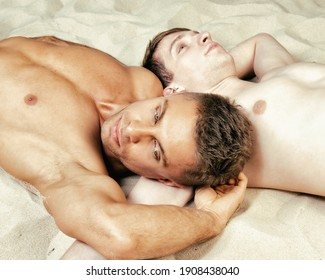 Vacation and Holidays. Young attractive gay couple on the beach.