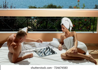 Vacation Honeymoon Getaway. Happy romantic couple on the beach at sun. Romantic holidays. Youth and vacation.Chess playing. Erotic sexy game. Adult. Sensual. Romantic lovers. Tourism, travel. Sexy