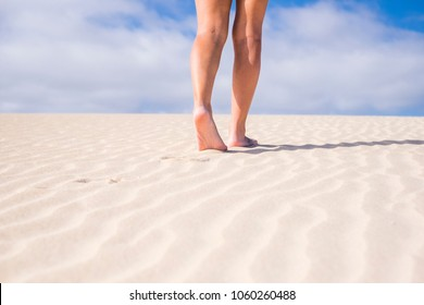 vacation nude, naturism concept with legs and feet walking in the soft sand with blue sky in the background. beautiful part of woman and freedom concept