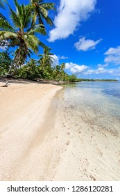 Vacation on beautiful and lonely sandy beach in a paradise on Samana, Dominican Republic  in the Caribbean with palms, sky, ocean and clouds and beautiful clear water in the foreground