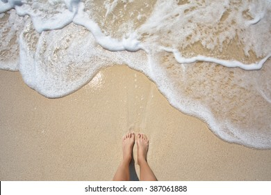 Vacation on ocean beach, feet on sea sand