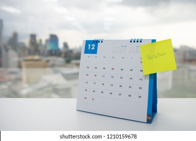 Vacation on paper note stick on the calendar of December for year end holidays concept
