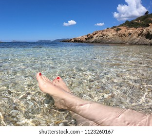 Vacation on sardinia beach in Italy. Woman's legs in the clear ocean water. First person perspective