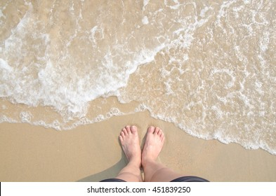 Vacation on summer ocean beach, feet on sea sand with bubble float wave