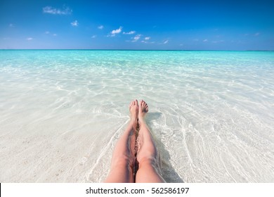Vacation on tropical beach in Maldives. Woman's legs in the clear ocean water. First person perspective