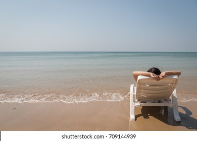 Vacation on tropical beach Woman rest on the beach bed with clear ocean water background