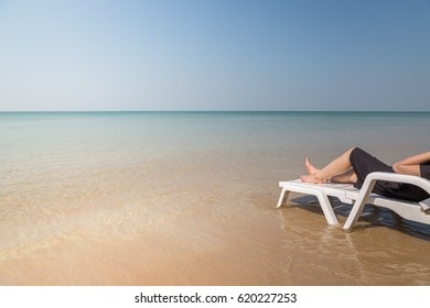 Vacation on tropical beach Woman's legs on the beach bed with clear ocean water background