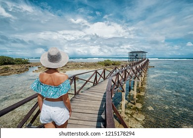 Vacation on tropical island. Back view of young woman in hat enjoying sea view from wooden bridge terrace, Cloud 9 Surfing Spot, Siargao Philippines.
