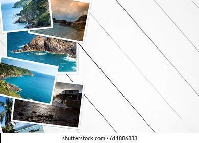 Vacation pictures on a wooden white table. View from above.