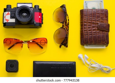 Vacation planning. Bright yellow one-color background with tourist's accessories mock up, top view.Travel or tourism concept.