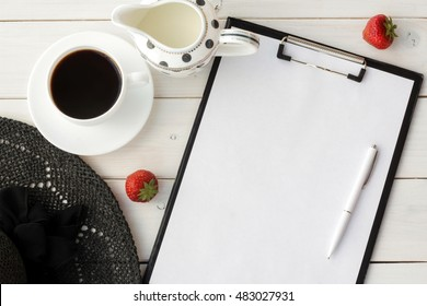 Vacation planning, coffee break, morning coffee, ideas, notes or plan  writing concept.   Desk  with office supplies, coffee cup, strawberries and women's  summer hat.  Space for text.  Top view.