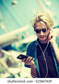 Vacation, relaxation, passion concept. Young fashionable blonde in sunglasses man relaxing, listening to music and enjoying beautiful, sunny weather. Outdoor shot