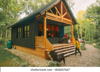 Vacation rental forest lodge countryside cabin by the lake for holidays in the wilderness. Woman entering her house home away from home.