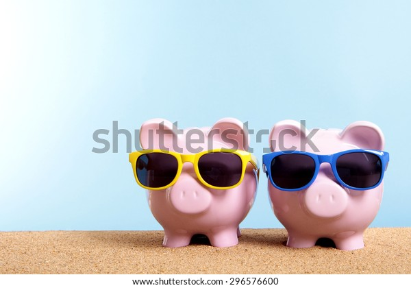Vacation or retirement saving money concept, piggy banks on beach.  Copy space.